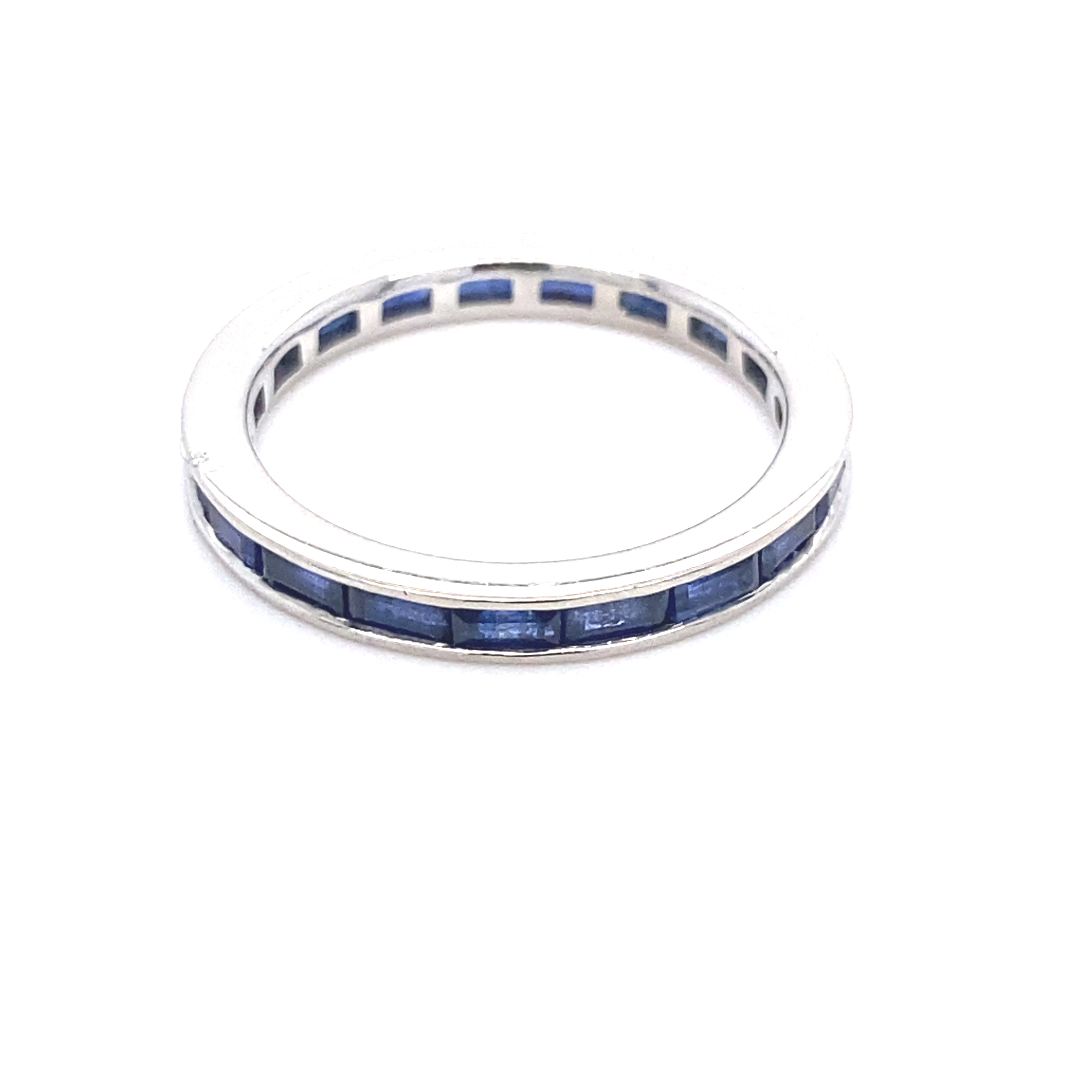 A baguette sapphire and platinum full eternity ring